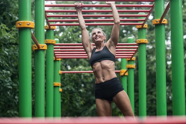 Chica haciendo ejercicios en la barra horizontal. la mujer se dedica a hacer ejercicio