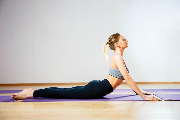 Chica haciendo ejercicios de calentamiento para la columna vertebral, flexión hacia atrás, arqueando estirándola de nuevo trabajando en clase de yoga.