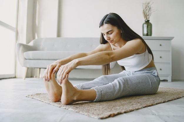 Chica haciendo ejercicios de yoga en casa cerca de un sofá y una ventana en ropa deportiva