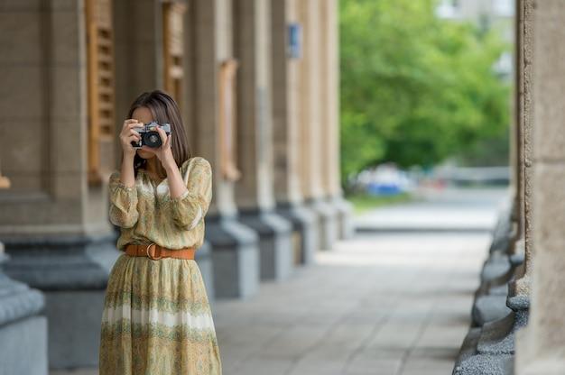 Chica haciendo fotos con cámara retro