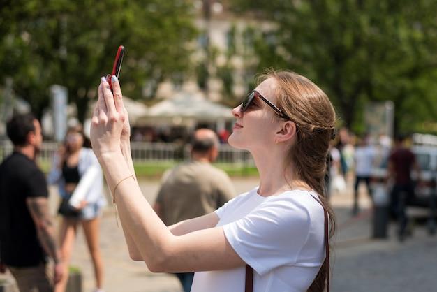 Chica haciendo fotos en el teléfono. mujer joven haciendo selfie. blogger