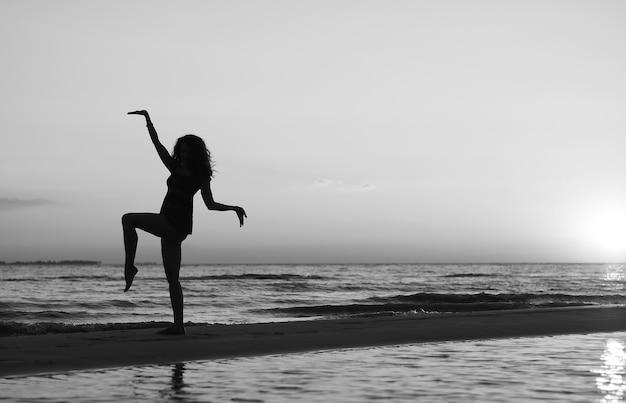 Chica haciendo gimnasia en la playa al atardecer