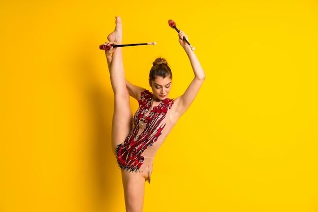 Chica haciendo gimnasia rítmica con mazas.