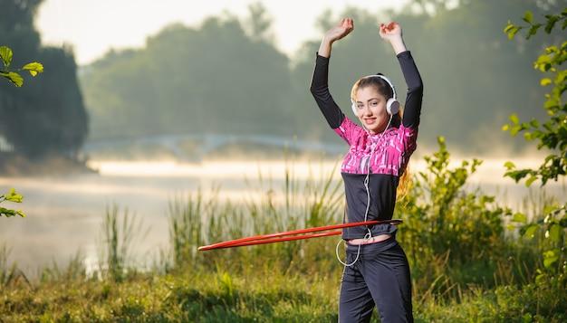 Chica haciendo hula hoop al aire libre cerca del lago
