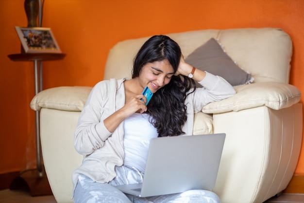 Chica haciendo pagos en línea usando una computadora portátil para comprar en casa