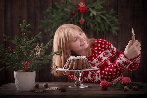 Chica haciendo selfie con pastel de navidad