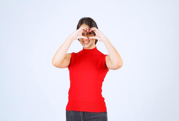 Chica haciendo signo de corazón con la mano y mirando a través de él.