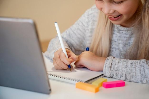 Chica haciendo sus deberes en concepto de tableta