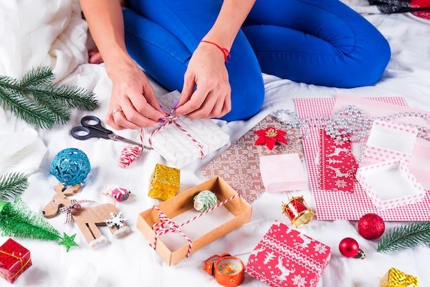 Chica haciendo tarjetas de navidad y decoraciones para la familia y el árbol de navidad. celebraciones, fiesta de cumpleaños, regalos,
