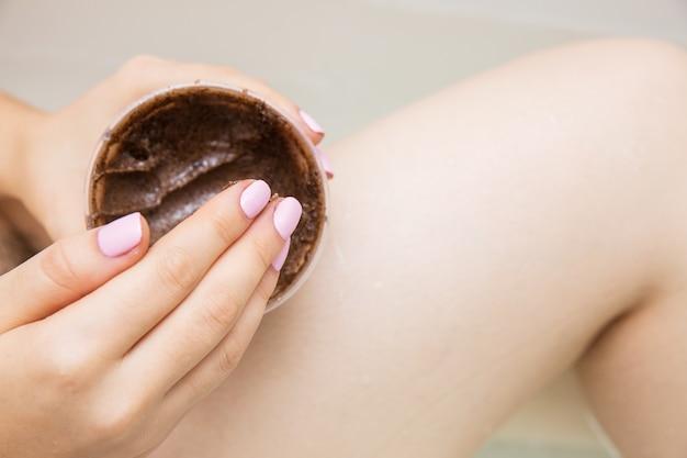 Chica haciendo tratamientos de belleza en el baño. exfoliante de café para los pies