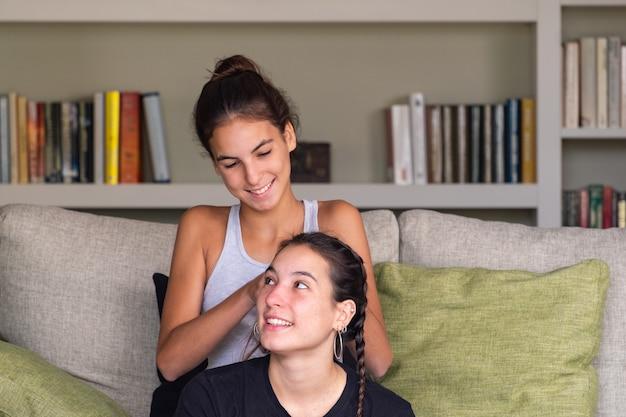 Chica haciendo trenzas de pelo en la cabeza de su hermana
