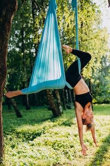 Chica haciendo yoga mosca en el árbol al aire libre.