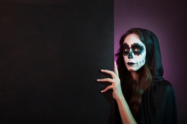 Chica de halloween con makeup detrás de pared