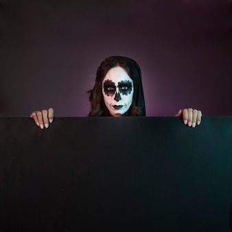 Chica de halloween con makeup detrás de tabla grande