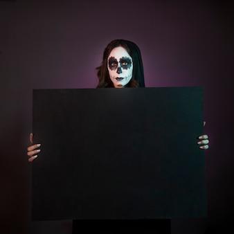 Chica de halloween con makeup sujetando tabla grande