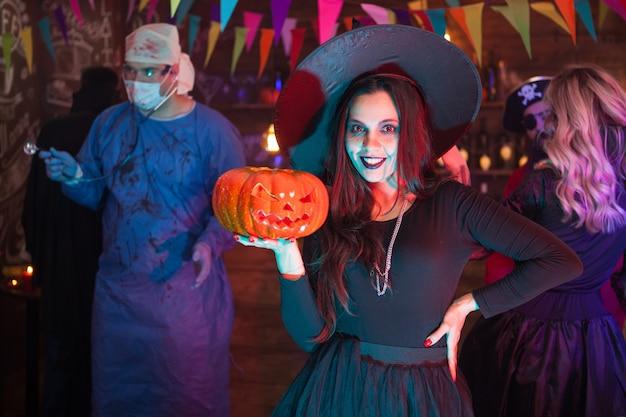Chica de halloween en vestido de bruja con un gran sombrero sosteniendo una calabaza. médico aterrador en el fondo cubierto de sangre.