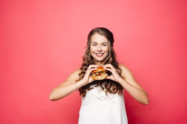 Chica hambrienta con la boca abierta comiendo hamburguesas grandes.