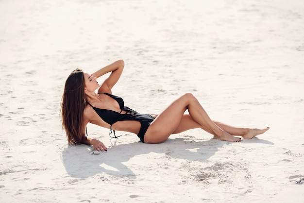 Chica hermosa atractiva con cuerpo de gimnasio bronceado perfecto tumbado en la playa de arena.