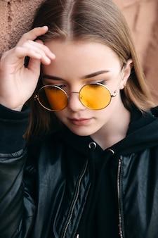 Chica hermosa chica de moda en gafas de sol amarillas en calle de la ciudad