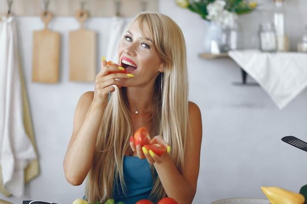 Chica hermosa y deportiva en una cocina con verduras