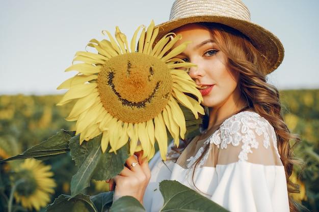 Chica hermosa y elegante en un campo con girasoles