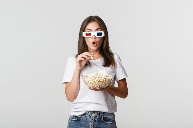 Chica hermosa emocionada e impresionada comiendo palomitas de maíz, viendo películas en gafas 3d.
