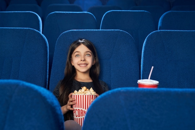 Chica hermosa y feliz viendo películas con palomitas de maíz en el cine.