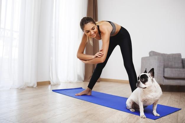Chica hermosa fitness hacer ejercicios deportivos con perro