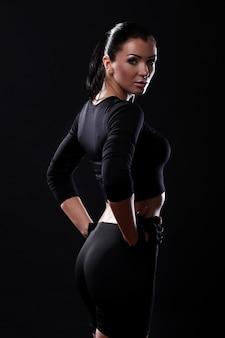 Chica hermosa fitness sobre fondo negro