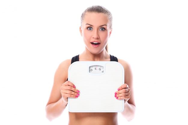 Chica hermosa fitness sosteniendo escalas