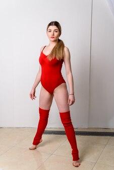Chica hermosa gimnasta en traje rojo.