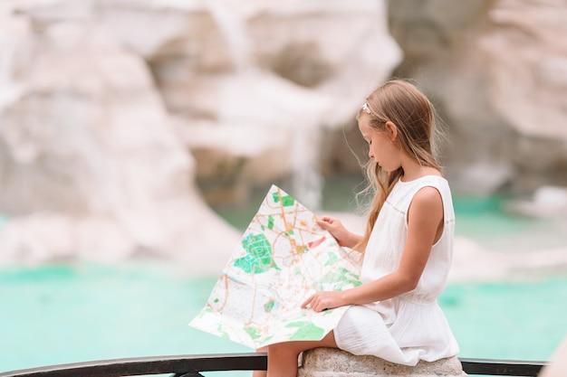 Chica hermosa joven cerca de la fuente fontana di trevi con mapa de la ciudad