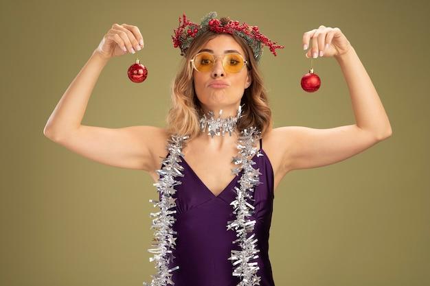 Chica hermosa joven confiada con vestido púrpura y gafas con corona y guirnalda en el cuello sosteniendo bolas de árbol de navidad aisladas sobre fondo verde oliva