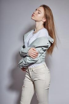 Chica hermosa joven modelo en jeans blancos azules