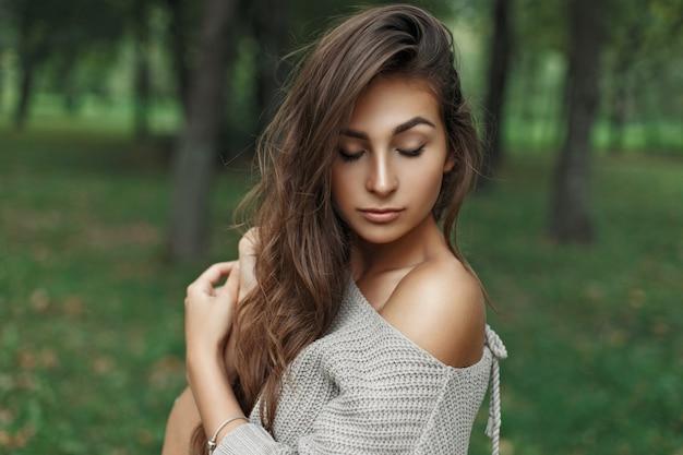 Chica hermosa joven modelo con peinado en un suéter de punto en el parque
