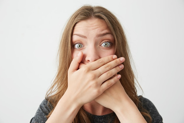 Chica hermosa joven sorprendida que cierra la boca detrás de las manos.