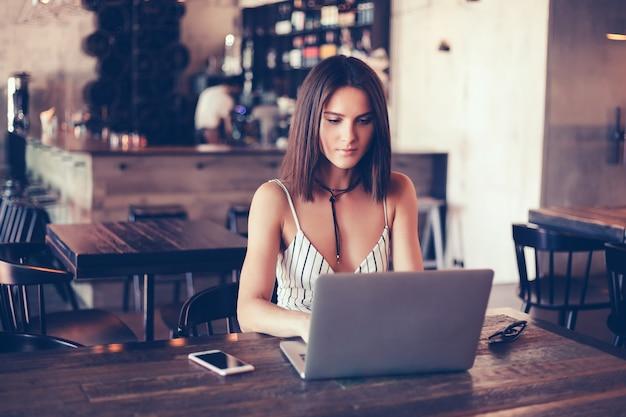 Chica hermosa joven usa una laptop en café, navegando en internet