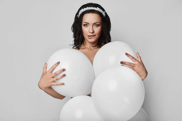 Chica hermosa modelo desnuda de moda con globos blancos