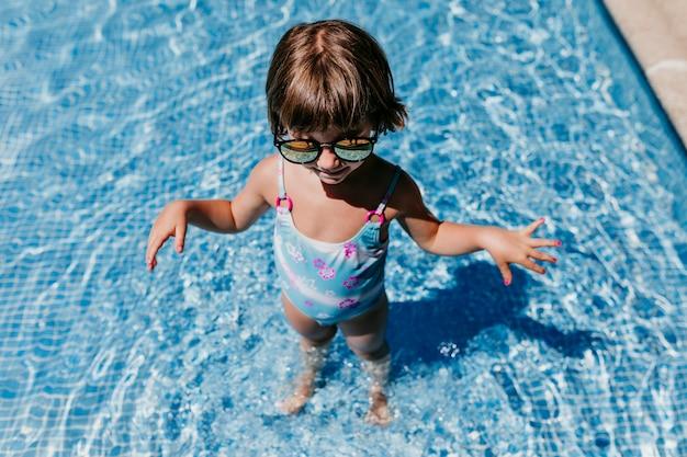 Chica hermosa niña en la piscina con gafas de sol modernas. diversión al aire libre. concepto de verano y estilo de vida
