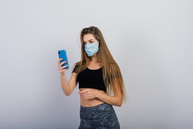 Chica hermosa de pelo largo con máscara quirúrgica mirando el teléfono inteligente y haciendo ejercicio físico.