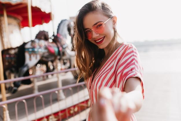Chica hermosa tímida en gafas de sol de corazón de pie junto al carrusel. retrato al aire libre de mujer alegre en traje de rayas sonriendo