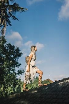 Chica hippie con el pelo largo y rubio en un vestido en el techo.