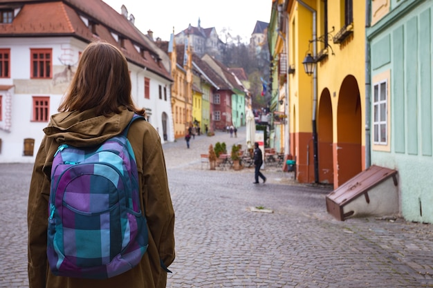 Chica hipster caminando por la hermosa calle del casco antiguo de sighisoara, rumania