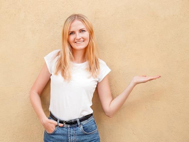 Chica hipster con camiseta blanca en blanco y jeans posando contra la pared de la calle áspera, estilo de ropa urbana minimalista, mujer muestra a mano