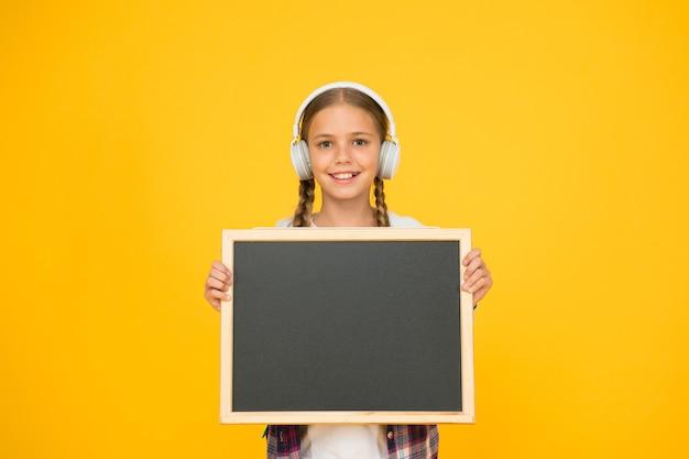 Chica hipster mantenga pizarra vacía. colegiala estilo casual mostrar información. centro comercial de la escuela. música en sus auriculares. niño presentando proyecto. bienvenido a nuestra escuela moderna. sueño grande.