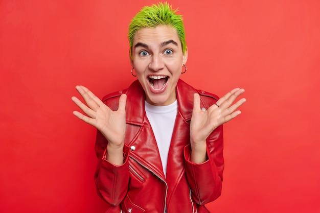 Chica hipster positiva con cabello corto verde extiende las palmas de las manos exclama de felicidad reacciona ante noticias asombrosas no puede creer en una revelación impactante usa poses de chaqueta de cuero contra la pared roja