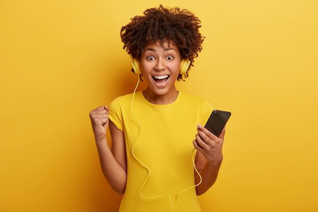 Chica hipster positiva escucha grabación de audio con volumen alto