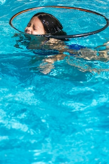 Chica entre hula hoop nadando en la piscina