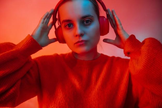 Una chica con una iluminación de colores brillantes escucha música con auriculares.
