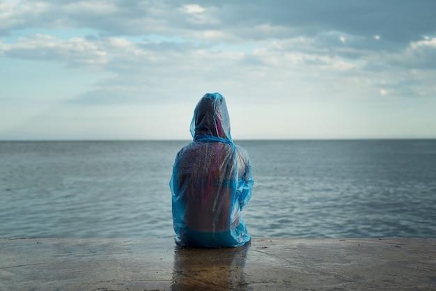 Chica en impermeable transparente de pvc sentado en la playa solitaria, día lluvioso en la playa